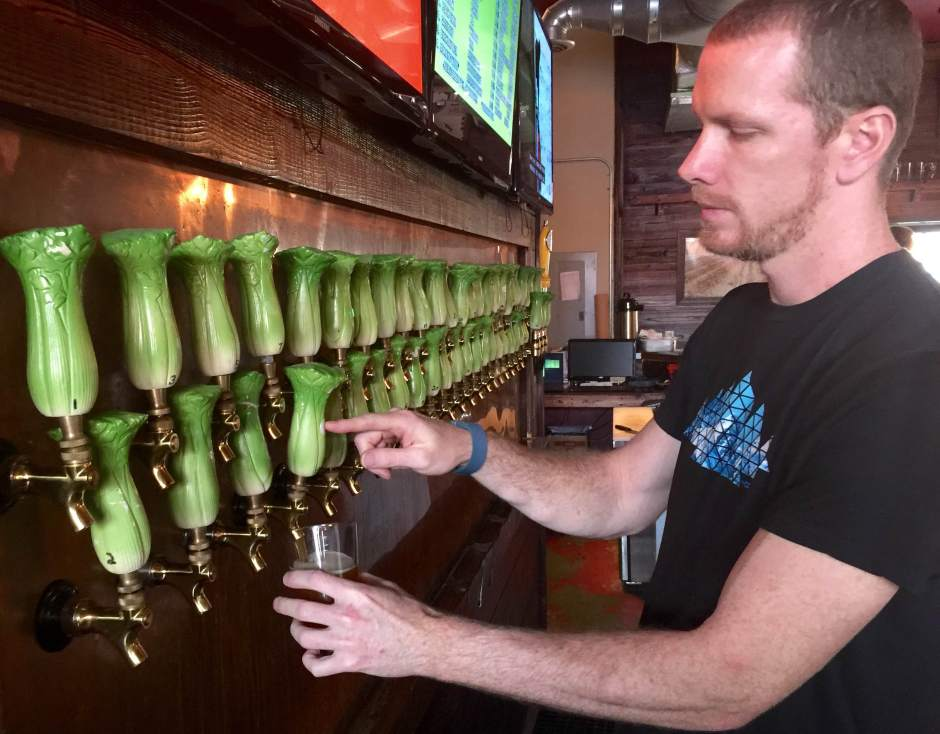 cutline: Chris Mann of Celery City Craft pours a beer for a customer. The bar's name pays homage to Sanford's history as a major celery producer, as do the celery stalk tap handles for the 51 different craft beers. Photo by Dan Ping