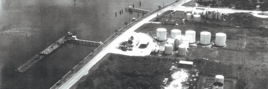 Aerial photo from the 1950s, shows a truck stop – belived to be named the Dew Drop Inn – in the spot where the brick round building sits today (lower left corner of photo). The Standard Oil fuel farm is shown where the Park at Revello apartments are located today (formerly the Sailpointe Apartments).