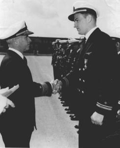 CLICK TO ENLARGE.  Vice Admiral John McCain Sr., left, presents the Navy Cross to Lt. Richard Fowler. The original caption from this U.S.  Navy photo read: For extraordinary heroism as Pilot of a Fighter Plane in Fighting Squadron FIFTEEN, attached to the USS Exxex, during operations against enemy Japanese forces in the Battle for Leyte Gulf,on October 25, 1944. Undaunted by intense antiaircraft fire, Lieutenant (then LTJG) Fowler carried out an attack against major hostile fleet units, scoring a direct bomb hit on a Japanese battleship, and contributing to the success of the mission. By his skill as an airman, and devotion to duty throughout, Lt. Fowler upheld the highest traditions of the United States Naval Service.