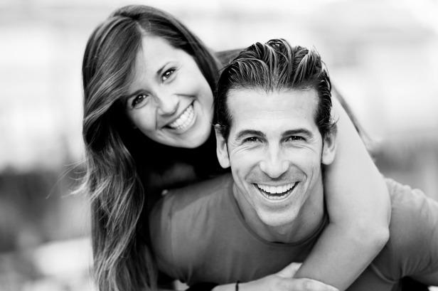 Smiling young man piggybacking his pretty girlfriend
