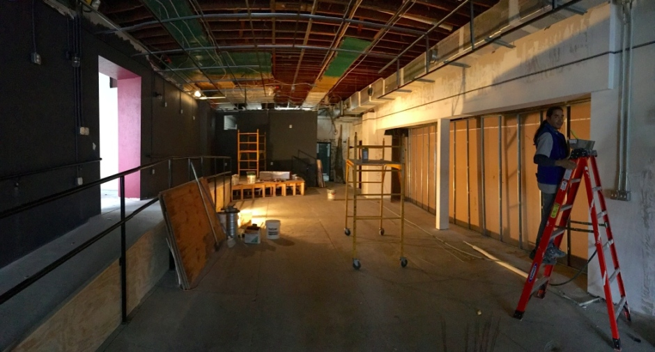 Standing near the entrance and looking west at 118 S. Park Ave., the space which once was home to the Emerald Hen Irish Pub and later the Black Swan Tavern. On the right, the recessed area is a temporary wall that will be removed and open up into The Alley Blues Bar. The new stage for The Alley is located at the back left of the photo. On the left, is the ramp and entrance into the old bus station/gas station next door that will become the new barbecue restaurant.